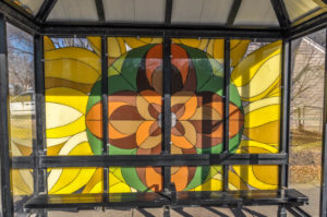 Abstract Sunflower design on Bus Shelter - north side of 21st Street North at Kansas - painted glass - artist(s) unknown 2010